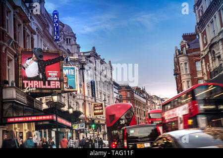 Shaftesbury Avenue London slow traffic jam Theatreland West End theatres busy heavy pollution diesel fumes gridlock with red buses, taxis and people in a busy Shaftesbury Avenue at dusk, with clear blue sky and pollution below. West End London UK - Stock Image
