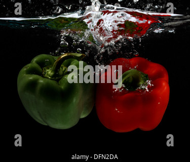 Red and green bell peppers splashing in to water, frozen using flash. - Stock Image