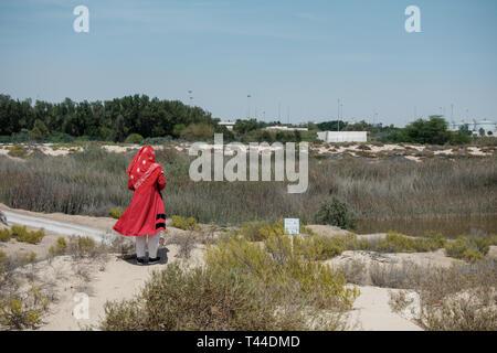 April, 6, 2019: Abu Dhabi, UAE: Female tourist wearing red gown at Al Wathba Wetland Reserve Abu Dhabi, UAE - Stock Image