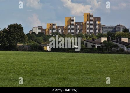 Skyline of social melting pot, Cologne Chorweiler high rise buildings, 70s design, from countryside, meadow in foreground. - Stock Image