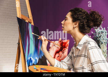 Creative artistic beautiful woman painting at home, holding palette - Stock Image
