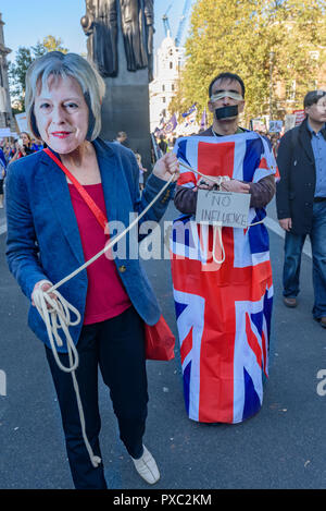 London, UK. 20th October 2018. A woman in a Theresa May mask leads a tied, blindfolded and gagged Britain at the end of the People's Vote March calling for a vote to give the final say on the Brexit deal or failure to get a deal. They say the new evidence which has come out since the referendum makes it essential to get a new mandate from the people to leave the EU. With so many on the march the crowding meant many failed to reach Parliament Square and came to a halt in Whitehall. Peter Marshall/Alamy Live News - Stock Image