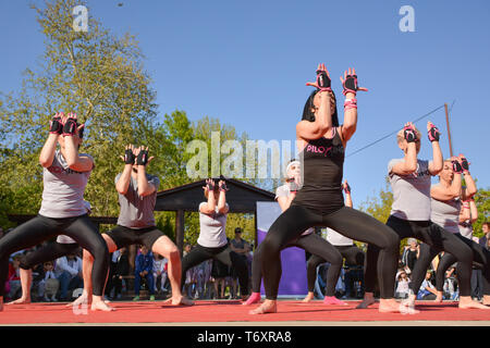 Nis, Serbia - April 20, 2019 Large group of happy beutiful people with instructor training Piloxing sport on sunny spring day - Stock Image