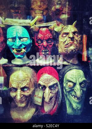 Ghoulish masks in a window display. It must be Halloween Time. Not recommended for people with a nervous disposition! Photo Credit - © COLIN HOSKINS. - Stock Image