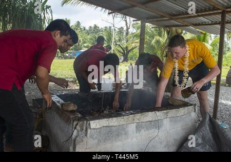 RONGRONG, Republic of the Marshall Islands (March 18, 2018) U.S. Navy Master-at-Arms 3rd Class Andrew Jones helps Marshallese students at Rongrong Christian School smoke a pig during a host nation engagement during Pacific Partnership 2019. Pacific Partnership, now in its 14th iteration, is the largest annual multinational humanitarian assistance and disaster relief preparedness mission conducted in the Indo-Pacific. Each year, the mission team works collectively with host and partner nations to enhance regional interoperability and disaster response capabilities, increase stability and securi - Stock Image