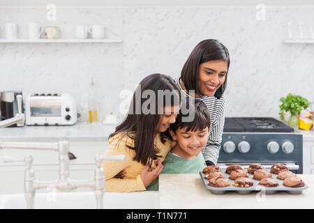 Mother and children baking chocolate muffins - Stock Image