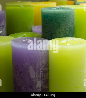 Many colorful unlit candles close up, decorative background - Stock Image