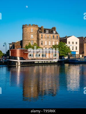 Leith Docks, Edinburgh, Scotland, United Kingdom, 16th May 2019. UK Weather: A glorious sunny day comes to an end over the harbour area in Leith with buildings and barges on The Shore lit up by the last rays of the sun reflected in the Water of Leith river. Credit: Sally Anderson/Alamy Live News - Stock Image