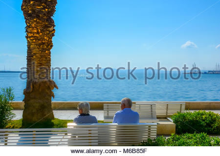 An older couple sits on a bench and enjoys a view of the Adriatic Sea at the Riva Promenade on the Dalmatian Coast - Stock Image
