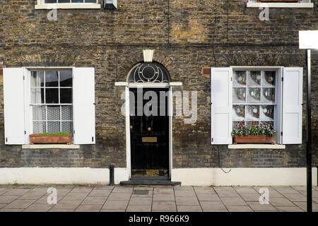 Christmas decorations and viola flowers in window box outside a house with black door, fanlight and shutters on window South London UK  KATHY DEWITT - Stock Image