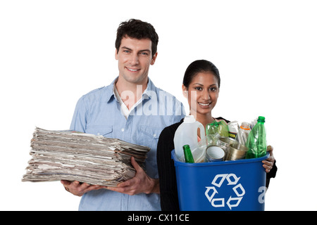 Man and woman holding recycling bin with bottles and newspapers - Stock Image