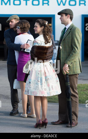 Chichester, West Sussex, UK. 14th Sep, 2013. Goodwood Revival. Goodwood Racing Circuit, West Sussex - Saturday 14th September. A group of visitors to the Revival meeting stand outside the motor works in period clothing including fur wrap and seamed stockings. Credit:  MeonStock/Alamy Live News - Stock Image