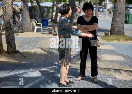 Chinese woman in traditional dress talking to Chinese female in Western clothes. Concept of old v new - Stock Image