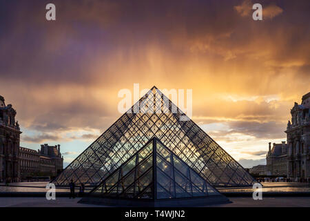 Clearing rainstorm over the iconic glass pyramid in the courtyard of Musee du Louvre, Paris, France - Stock Image
