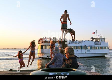Teens jumping off dock at dusk, Fair Harbor, Fire Island, NY, USA - Stock Image