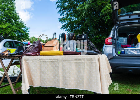 A table next to a car at a carboot sale with various different ladies handbags displayed for sale - Stock Image