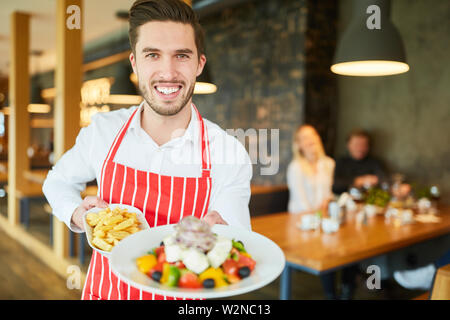 Young waiter serving in restaurant as greek salad with feta appetizer - Stock Image