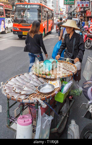 Bangkok, Thailand - 7th March 2017: Street food vendor pushing her cart down Yaowarat road. This is the main road through Chinatown. - Stock Image