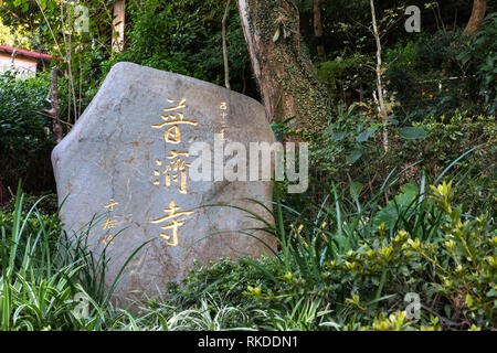 Stone with the name Pu Chi Temple in gold at the entrance to the temple, a Shingon Buddhist temple in Beitou Distirict in northern Taipei. - Stock Image