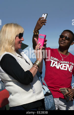 Two people, (one black, one white), on Table Mountain, Cape Town, taking selfies with their mobile phones. - Stock Image