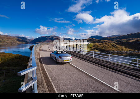 A convertible sports car driving over the Kylesku Bridge, North coast 500 Sutherland, Highland, Scotland, UK - Stock Image