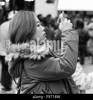 A female Japanese tourist takes a photograph with her phone at the Sensō-ji temple (金龍山浅草寺) in Asakusa, Tokyo. - Stock Image