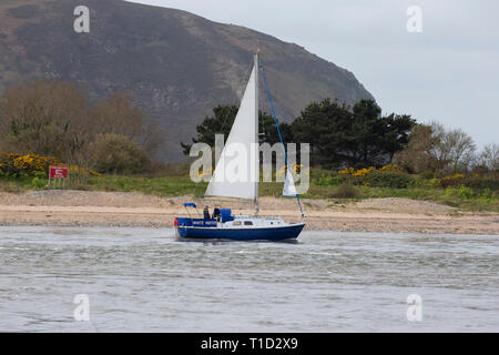 Leisure yacht leaving Conwy estuary in North Wales and sailing past Conwy Morfa - Stock Image