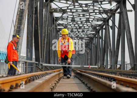 (190423) -- CHONGQING, April 23, 2019 (Xinhua) -- Tang Jinhua (R) checks rails on the previous Baishatuo Yangtze River railway bridge in Jiangjin of southwest China's Chongqing Municipality, April 23, 2019. The previous Baishatuo Yangtze River railway bridge, completed in 1959, will stop service after April 24. All trains will run on the new double decker steel truss cable stay railway bridge after that day. The new bridge has 4 tracks on the upper deck for passenger trains with a designed speed of 200 kilometers per hour and 2 tracks on the lower deck for cargo trains with the designed speed  - Stock Image