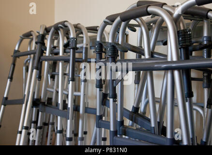 A group of walkers hanging up together in a physiotherapy space or nursing home - Stock Image