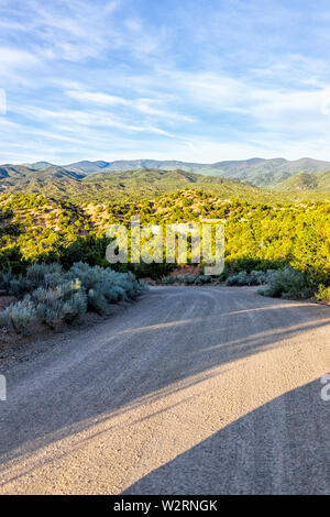 Sunset Santa Fe, New Mexico mountains vertical view in Tesuque with golden hour light on green plants and dirt road to residential community - Stock Image