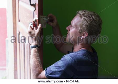 A German expat works on a door lock in a rental property in Jinotega, Nicaragua - Stock Image