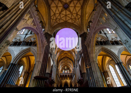 Salisbury, Wiltshire, UK. 11th Dec 2018. From Darkness to Light inside Salisbury Cathedral in Wiltshire England. 'The Light' an installation by Richard McLester hangs high above the nave and is seen here reflected in the Cathedral Font by William Pye. The 4 metre illuminated globe glows, flowing from one colour to another for Advent and through Christmas until February 2019. Credit: BRIAN HARRIS/Alamy Live News - Stock Image