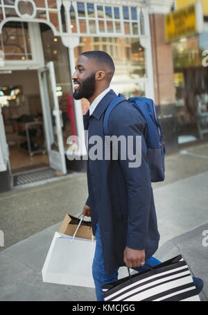 Smiling young man walking along storefront, carrying shopping bags - Stock Image