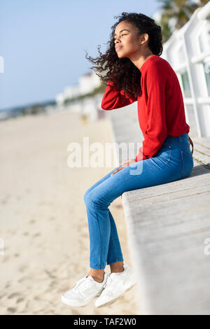 Young woman sitting on beach promenade - Stock Image