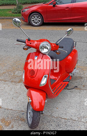Red Vespa motor scooter parked on a residential street, Vancouver, BC, Canada - Stock Image