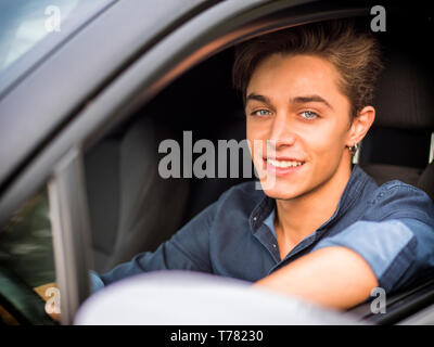 Handsome blue eyed young man sitting in his car, looking at camera - Stock Image