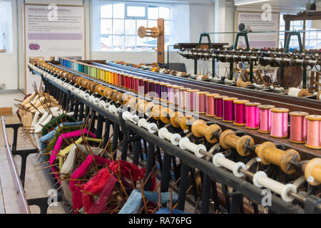 Whitchurch Silk Mill in Hampshire, UK. Interior of the museum with colourful yarns wound onto reels or bobbins. - Stock Image