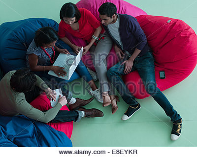 Business people in bean bag chairs looking at laptop - Stock Image