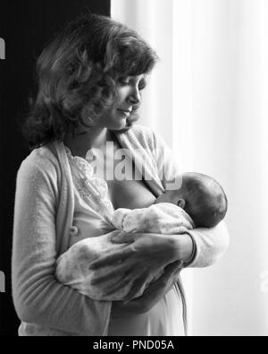 SERENE YOUNG MOTHER STANDING HOLDING NURSING INFANT BABY SON - b25535 HAR001 HARS SONS JOY LIFESTYLE CELEBRATION FEMALES HEALTHINESS HOME LIFE FULL-LENGTH HALF-LENGTH LADIES PERSONS CARING MALES SERENITY SPIRITUALITY B&W HAPPINESS WELLNESS STRENGTH BONDING CHOICE POWERFUL CONNECTION NOURISHMENT STYLISH AFFECTION GROWTH JUVENILES MOMS SERENE TOGETHERNESS BLACK AND WHITE BREAST FEEDING CAUCASIAN ETHNICITY HAR001 OLD FASHIONED - Stock Image