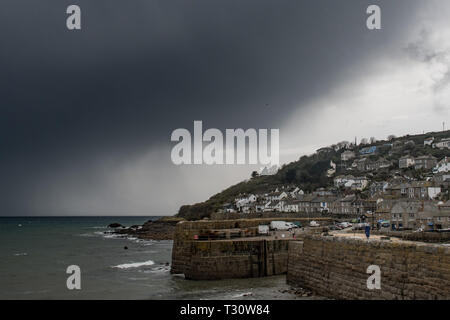 Storm clouds gathering over Mousehole village and sea Cornwall - Stock Image