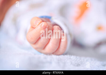 Newborn baby soft-focus tiny fist of an infant with a vintage analog Kodachrome feel. Happy Mothers Day Fathers Day new baby or parenting concept. - Stock Image