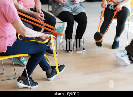 Active seniors stretching, exercising with straps - Stock Image