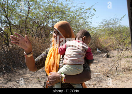 A Bishnoi woman giving directions while holding her baby. - Stock Image
