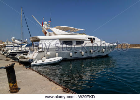 Chania, Crete, Greece, June 2019. Luxury motor cruiser berthed on the Old Venetian Harbour in Chania, Crete - Stock Image