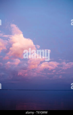 Pink clouds and blue sky at sunset with reflection on lake - Stock Image