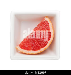 Slice of grapefruit in a square bowl isolated on white background - Stock Image