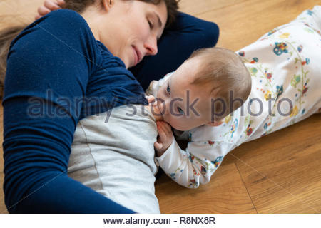 A mother looking lovingly at her baby daughter breastfeeding - Stock Image