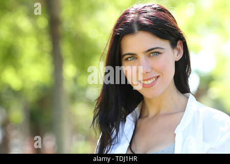 Beautiful brunnete woman looks at camera standing in a park - Stock Image