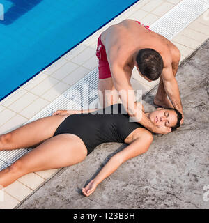 Lifeguard placing accident woman in recovery position. - Stock Image