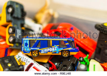 Poznan, Poland - December 9, 2018: Mattel Matchbox toy city bus in a container with other vehicles in soft focus.  - Stock Image